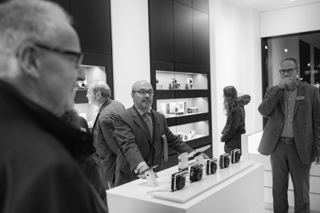Mr. Kaufmann, Leica's chairman of the supervisory board, standing proud behind a row of Leica's cheapest cameras.